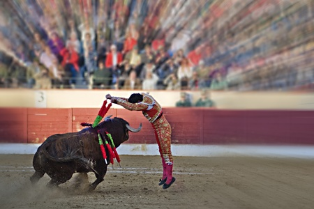 stabs: Spanish Fiesta: Bullfighting. During the Banderillas third, the matador attacks the bull on top and stabs him a pair of Banderillas Stock Photo