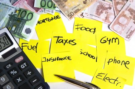 Calcolatrice e banconote su un tavolo pieno di post it giallo nota riferendosi costo della vita: mutui, tasse, carburante, cibo, scuola, telefono, assicurazioni, palestra e elettricità