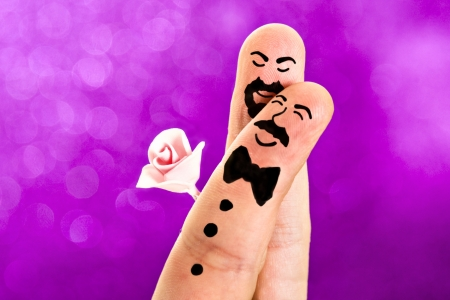Fingers with sweet faces painted featuring a wedding between a man with a moustache and a bowtie and a guy with a beard an a rose photo