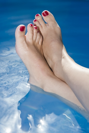 painted toes: Woman Feet with nails painted red in the water at the swimming pool Stock Photo