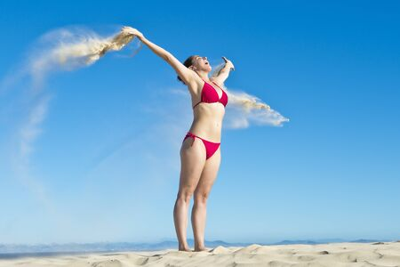 vibrating: Young Woman with extended arms and palms of her hands Pouring Beach Sand on a vibrant blue sky
