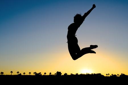 happy holidays: Vrouw Silhouet Springen op het strand bij zonsondergang verzenden van een concept van gezondheid, vreugde en vrijheid