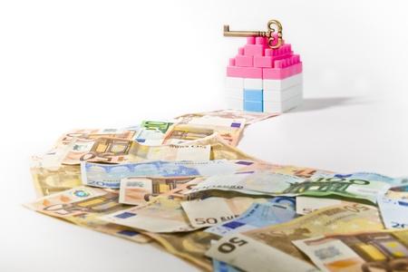 investment real state: Billetes de banco Camino a una casa en miniatura con clave aislado en el fondo blanco Foto de archivo