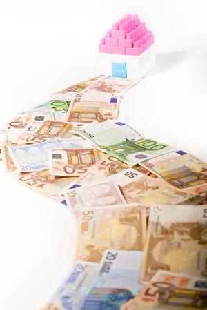 investment real state: Billetes Camino a una casa en miniatura con clave aisladas sobre fondo blanco