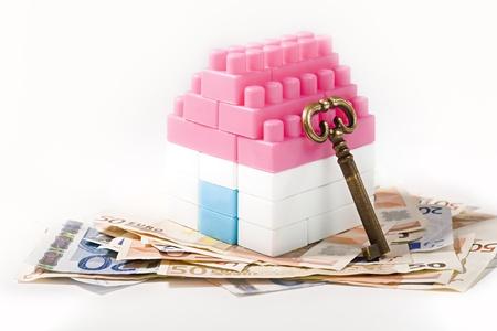 investment real state: Casa miniatura con llave sobre billetes de banco aislados en fondo blanco Foto de archivo