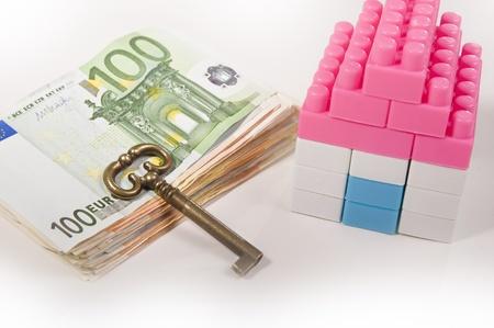 investment real state: Casa miniatura con clave en un Billetes de pilotes aislados sobre fondo blanco