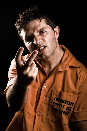 criminality: Angry Young Man in Prison acting obscene Stock Photo