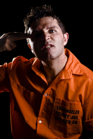 penal institution: Angry Young Man in Prison acting obscene Stock Photo