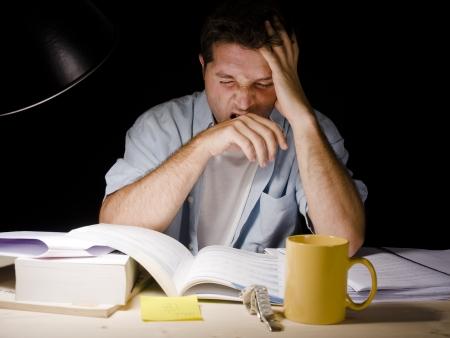 Jonge Man Geeuwen moe tijdens het studeren bij Nacht