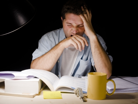 examination stress: Young Man Yawning tired while Studying at Night