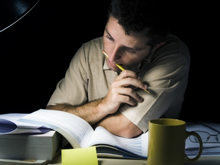 Young Man Studying at Night isolated on black background photo