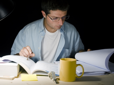 research study: Young Man Studying at Night isolated on black background