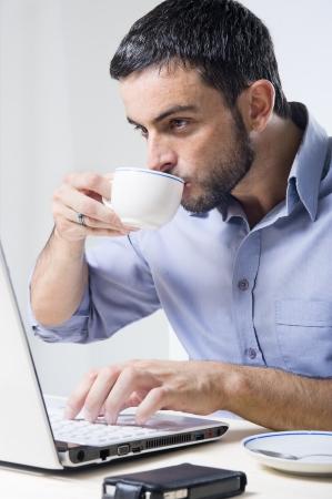 hombre tomando cafe: El hombre joven con barba de trabajo en la computadora port�til aislados en un fondo blanco Foto de archivo