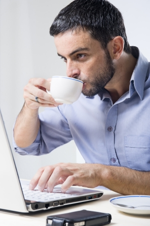 man drinking coffee: Young Man with Beard Working on Laptop isolated on a White Background