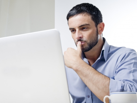 koncentrovaný: Mladý muž s vousy pracuje na notebooku izolovaných na bílém pozadí