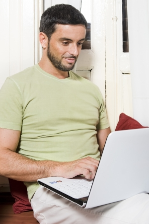 Happy Young Man Working on Laptop at Home  photo