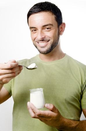 Happy Young Man with Beard Eating Yogurt Isolated on White Background photo