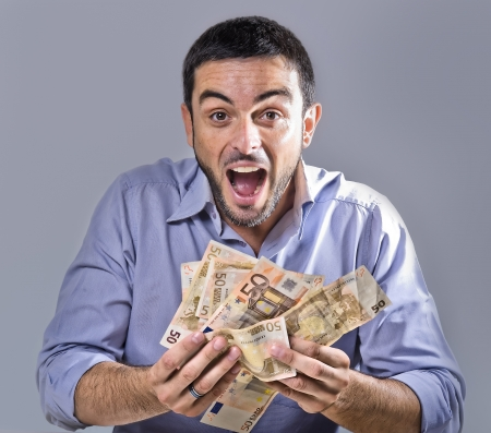 exultant: Exultant Young Man with Beard holding Banknotes isolated