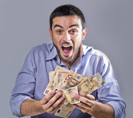 dinero euros: Exultante hombre joven con barba Billetes holding aislados Foto de archivo