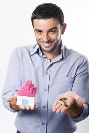 investment real state: Hombre joven hermoso que presenta Casa en miniatura y clave
