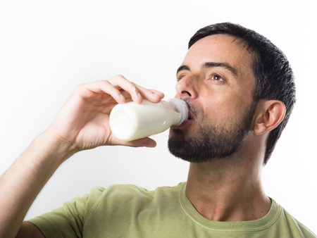 enyoing: Young Handsome Man with Beard drinking Milk and Yogurt isolated on White Background