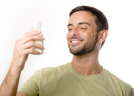 enyoing: Happy Young Handsome Man with Beard drinking Milk and Yogurt isolated on White Background Stock Photo