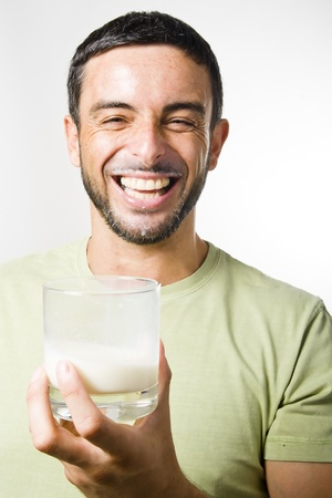 enyoing: Healthy Young Handsome Man with Beard drinking Milk isolated on White Background Stock Photo