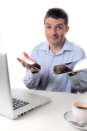 Businessman wearing a blue business shirt is overwhelmed with new technology, holding a smart phone and tablet sitting in front of his laptop on a white background photo