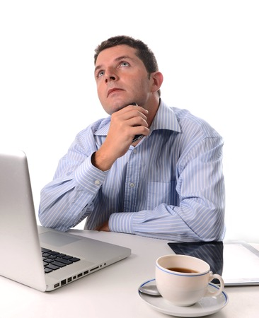 caucasian man wearing a blue business shirt  thinking and worried about his future with his smart phone in his hand at a desk on a white background  photo