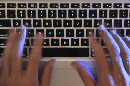 close up of a busy hands working on a laptop keyboard with the words help highlighted on the key board in blue photo