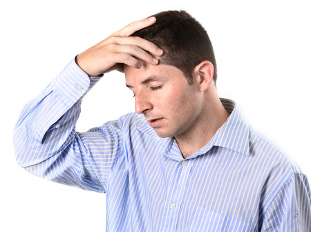 over worked: businessman wearing a blue business shirt is over worked and with a headache on a white background Stock Photo