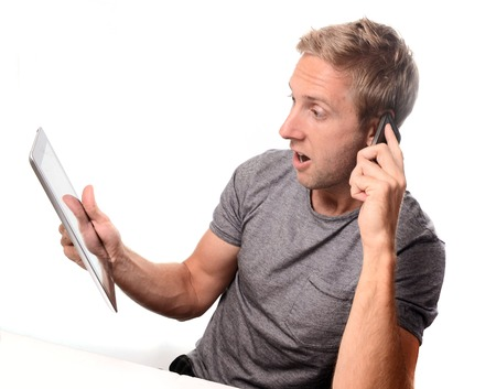 28: caucasian man wearing a grey t shirt holding a tablet on his phone looking shocked on a white background Stock Photo