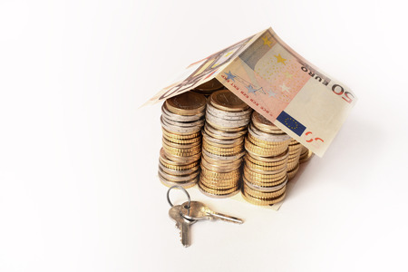 coins pile: Euro Coins pile House with banknote roof and key isolated on white