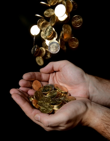 Man Hands full of money receiving a Rain of Coins isolated on black  photo