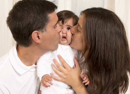 Mother and Father Kissing their Baby Girl photo