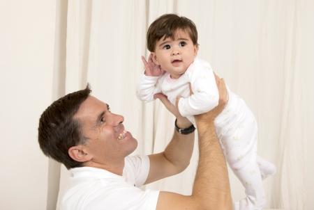 joyfull: Happy young father holding baby girl