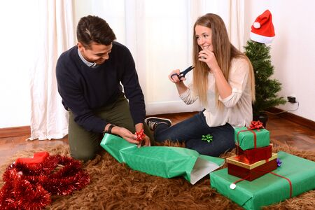 Young Happy Couple sitting on rug wrapping Christmas presents photo