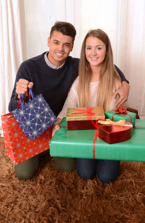 Young Happy Couple at home holding lots of Christmas Presents photo