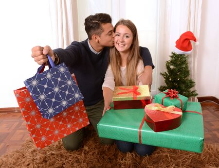 Young Happy Couple at home kissing and holding lots of Christmas Presents photo