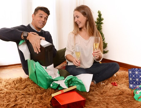 Young Happy Couple at home opening Christmas Presents photo