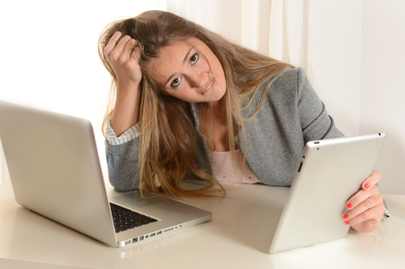Young stressed Business Woman with laptop and tablet  frustrated at work photo