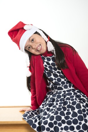 Cute Little Girl in Santa Claus hat sitting and Smiling at Christmas photo