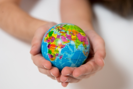 Little Kid holding World Globe on her Hands isolated on white background photo