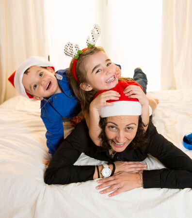 Happy Mum, daughter and little son playing at Christmas on bed photo