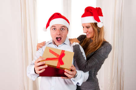Happy Young Man Opening Christmas Present with beautiful woman photo