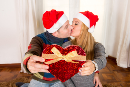 Romantic Young Happy Couple Christmas hats  kissing and Heart shaped Box  photo