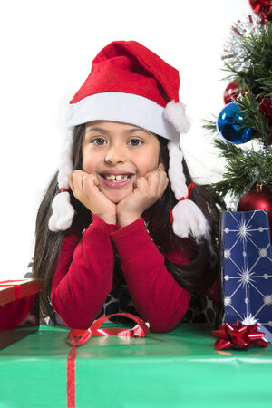 Cute Little Girl leaning on Presents smiling next to Christmas Tree photo
