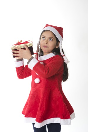 guessing: Cute Little Girl in Santa Claus costume shaking a Christmas Present guessing Stock Photo