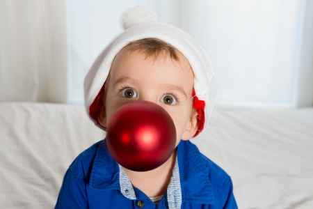cuttle little kid in Santa Claus hat playing with Christmas Bubble in Mouth photo