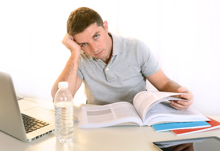 Overwhelmed  Stressed Student  with Book and Laptop photo